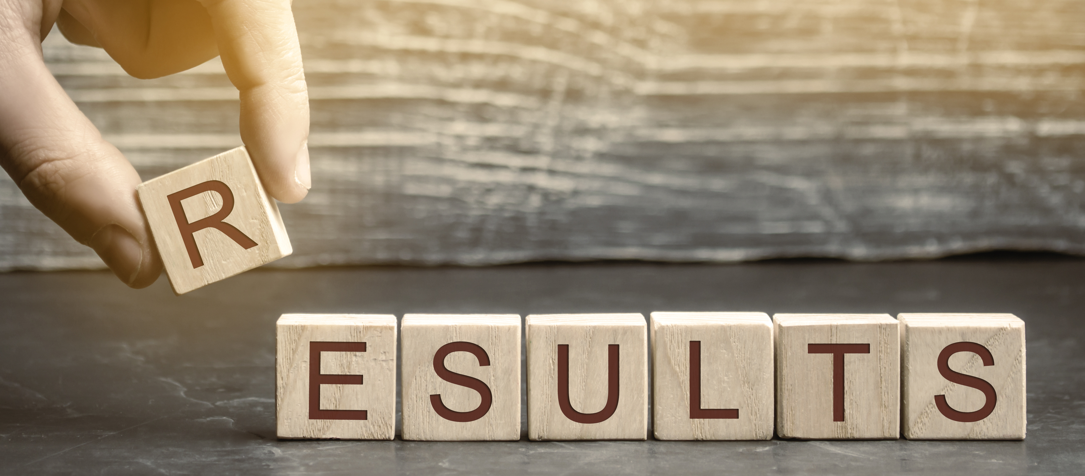 Businessman-Puts-Wooden-Blocks-That-Spells-Out-Results