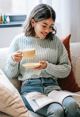 young lady sitting on couch drinking coffee and reading a magazine